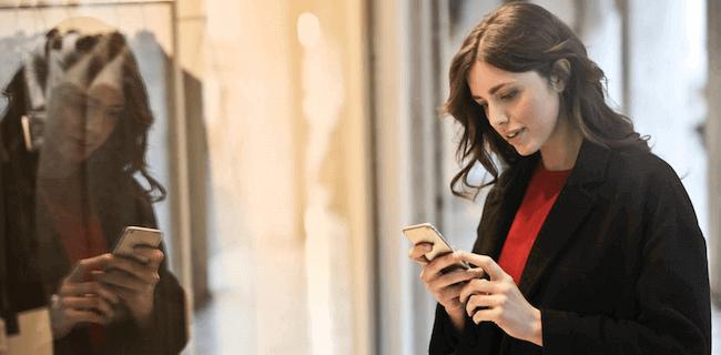 Mujer mirando el móvil frente a un escaparate.