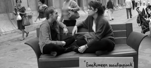 Chicas sentadas en un banco.