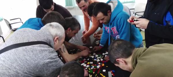 trabajadores realizando actividad con piezas Lego.